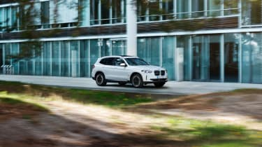BMW iX3 driving through city - front view