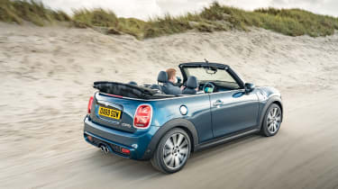 MINI Sidewalk Convertible driving on beach with roof down - rear view