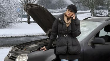 Woman on phone next to broken-down car