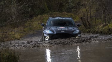Aston Martin DBX prototype wading through puddle - front view