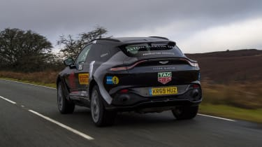 Aston Martin DBX prototype driving on road - rear view