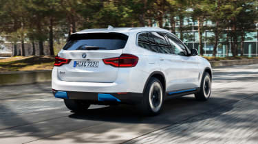 BMW iX3 driving through city - rear view