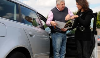 Two people talking over a car brochure