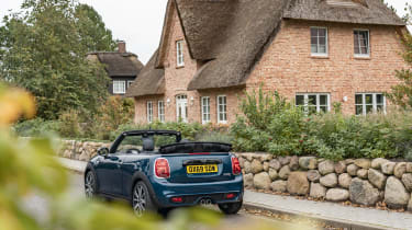 MINI Sidewalk Convertible parked next to cottage with roof down - rear view
