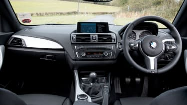 The dashboard features BMW's familiar iDrive infotainment system with standard sat nav
