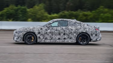 2020 BMW M4 prototype driving on racetrack - side view