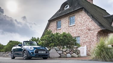 MINI Sidewalk Convertible parked next to cottage with roof down