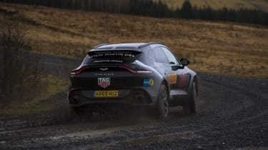 Aston Martin DBX prototype driving on dirt - rear view