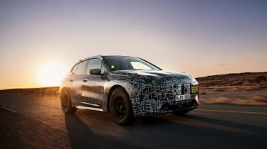 2021 BMW iNEXT electric SUV desert testing - dynamic front 3/4 at dusk