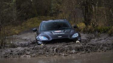 Aston Martin DBX prototype wading through puddle