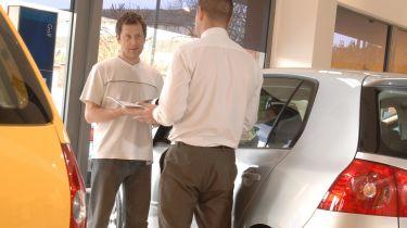 Car dealer and customer talking