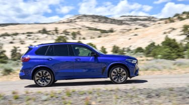 BMW X5 M Competition driving on gravel - side view