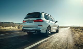 BMW X7 M50i rear view dynamic driving shot