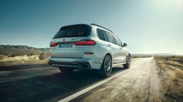 BMW X7 M50i rear view dynamic driving shot