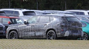 BMW X8 SUV in camouflage - side/rear view