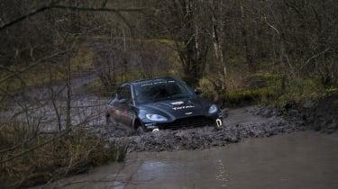 Aston Martin DBX prototype wading through huge muddy puddle