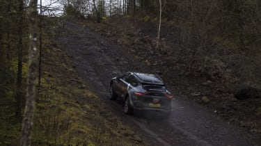Aston Martin DBX prototype driving uphill off-road - rear view