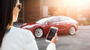 Woman looking at phone in front of a Tesla