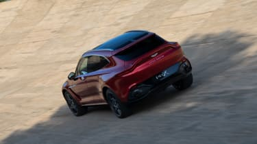 Aston Martin DBX driving on banked circuit - rear