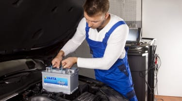 Man putting battery in car