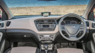 The i20's dashboard looks quite neat, but hard plastics mean parts of the interior feel cheap to the touch