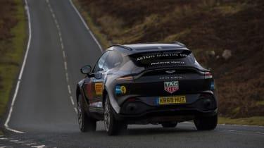 Aston Martin DBX prototype cornering on road - rear view