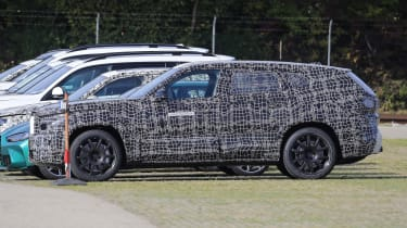 BMW X8 SUV in camouflage - side view