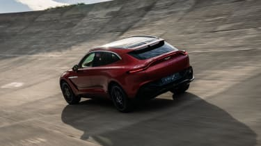Aston Martin DBX driving on banked circuit - rear view