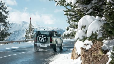 Land Rover Defender driving on road - rear view