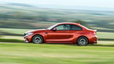 Orange BMW M2 driving - side view