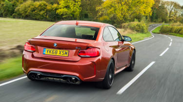 Orange BMW M2 driving - rear